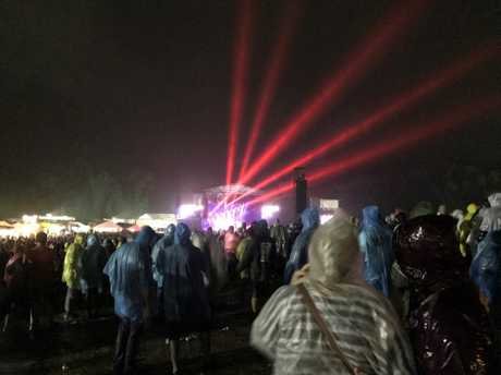 Concert-goers brave the rain to see Midnight Oil at Big Pineapple Fields.