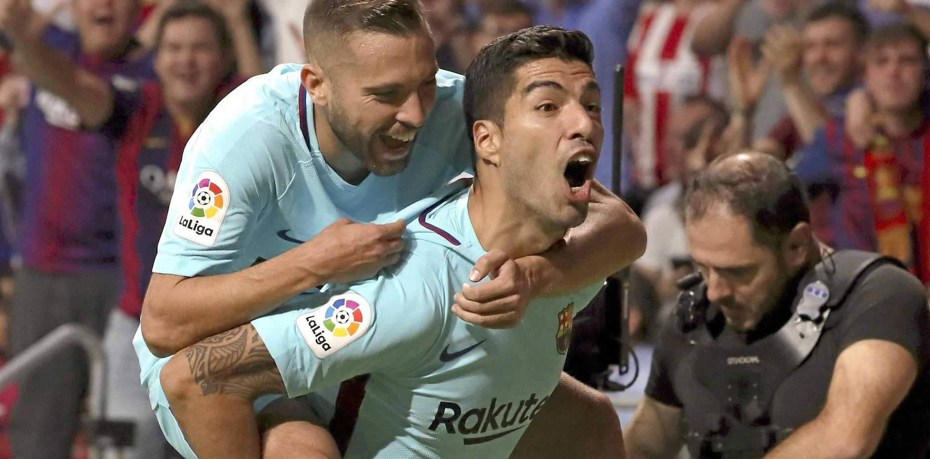 Barcelona's Luis Suarez (righgt) celebrates with his teammate Jordi Alba after scoring the equalising goal in the 1-1 draw with Atletico Madrid