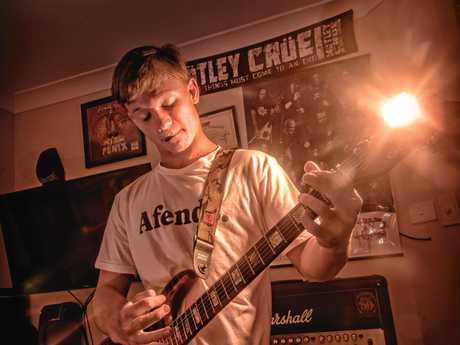 Maclean High School HSC Music student Travis Carlisle plays guitar in his room.