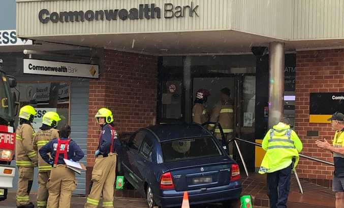 A car mounted the steps of Maclean's Commonwealth Bank and momentarily pinned an 81-year-old woman this morning.