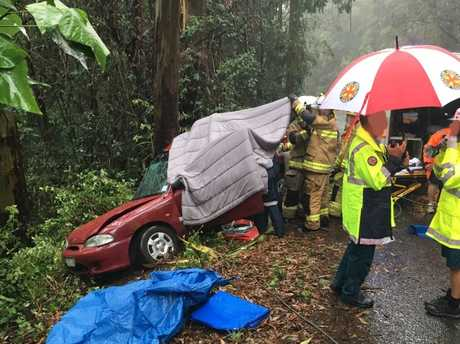 Emergency services crews work to release a woman from the wreckage of a crash near Maleny.