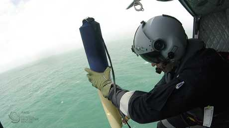 MISSING CREW: An RACQ Capricorn Helicopter Rescue Service officer deploys a self-locating datum marker buoy during the initial search for the vessel.
