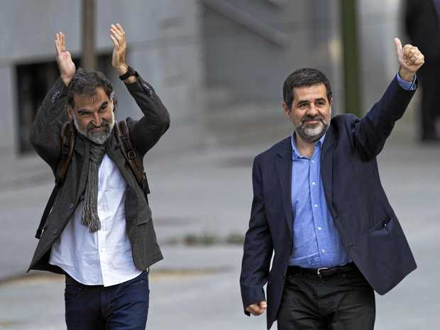 Jordi Cuixart, president of the Catalonian Omnium Cultural organisation and Jordi Sanchez, president of the Catalonian National Assembly, wave to supporters on arrival at the national court in Madrid.