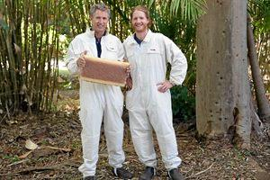 FLOW: Stu and Cedar Anderson, the inventors of the Flow Hive, suited up and holding a perfectly capped Flow Frame full of honey.