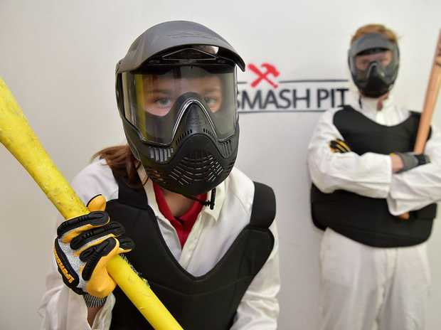 The Smash Pit has opened in Nambour. Customers can smash household items in a safe environment.Brittany Farley and Dalton Murray prepare for a whacking good time.