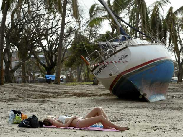 German tourists Caroline Herrmann and Nane Maurer sunbaking near a wrecked boat off the Airlie Beach Esplanade after Cyclone Debbie