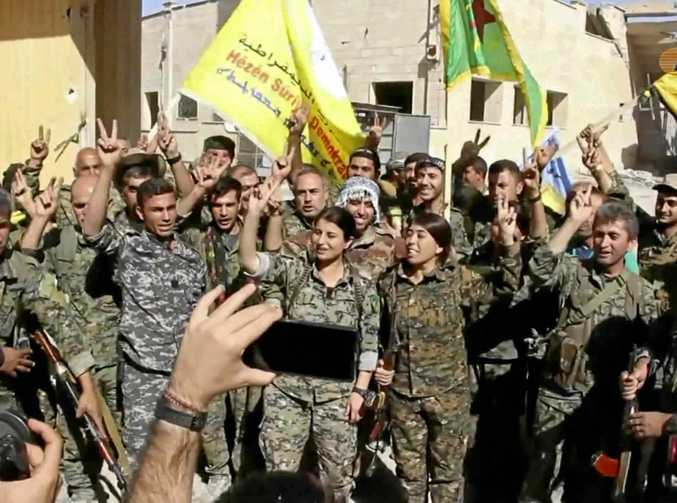This frame grab from video shows fighters from the US-backed Syrian Democratic Forces celebrating their victory in Raqqa, Syria.