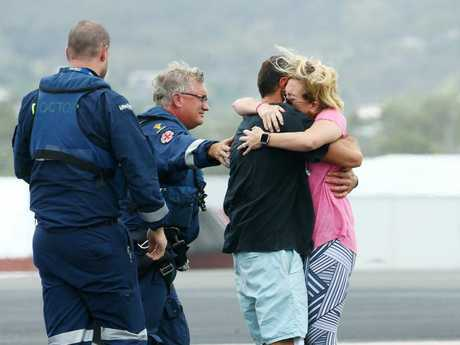REUNION: Capsized trawler survivor Ruben McDornan is reunited with his wife Sammy and his mother after landing at Gladstone Airport.
