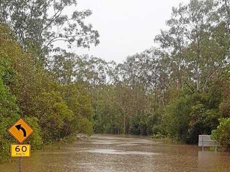 Road sections at the corner of Murphy Rd and Baldaw Rd, Captain Creek, washed away in rapid water.