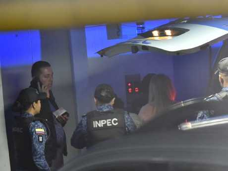 Cassie Sainsbury is led out of a police vehicle in an underground carpark beneath a Bogota court before being escorted to her hearing today. Picture: