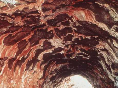Tourists walking through Undara wind tunnel lava tube in Queensland.