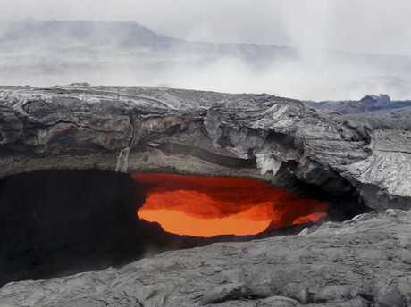This photo released by the U.S. Geological Survey shows a fluid lava stream within a solidified tube at the Kilauea volcano in Pahoa, Hawaii. Picture: US Geological Survey