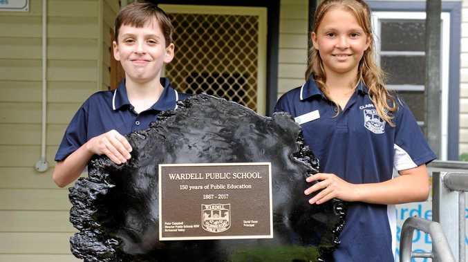 Wardell Public School students Tanesha Nugent and Sean Wilcox with the plaque that was unveiled during the school's 150th anniversary celebrations.