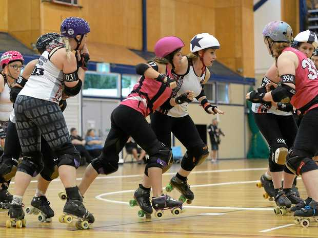 ON A ROLL: The Rocky Roller Derby team (in pink) takes on the Brisbane City Rollers in the Knocktoberfest at the weekend.