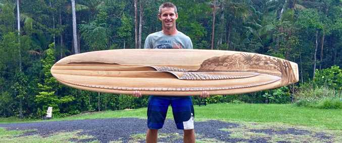 SHANE Christensen with a fine piece of artwork he would love to try to surf but probably never will given its value and the hours of work that went into its creation. It will be one of the pieces on show and for sale at the Surf Art Expo at Noosa this weekend.