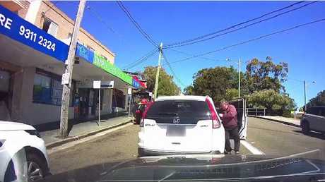 The driver gets out of his car to confront the man behind only to forget to apply his brakes. Picture: Dash Cam Owners Australia