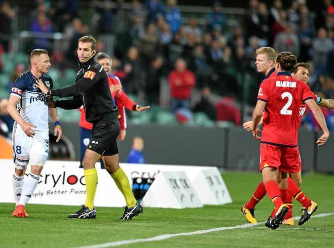 Fourth official Daniel Elder separates Victory's Besart Berisha and Adelaide's Jordan Elsey.