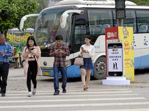 Pedestrians use their smartphones as they walk across a road in Chongqing, China.