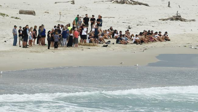 Family and friends hold a memorial for Dylan Carpenter at Fingal beach where the young surfer died. Picture Glenn Hampson