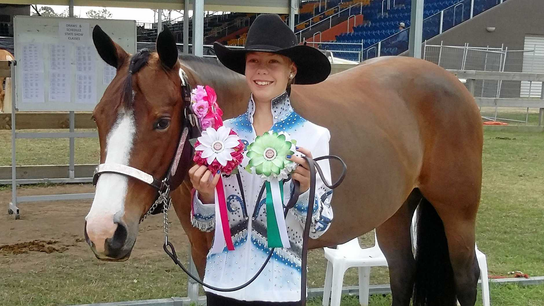 A 12-year-old Courtney Smallwood with Australian Champion horse in showmanship Hottie aka J Bar C Blazin Hot T received rosettes for winning in the showmanship competition.