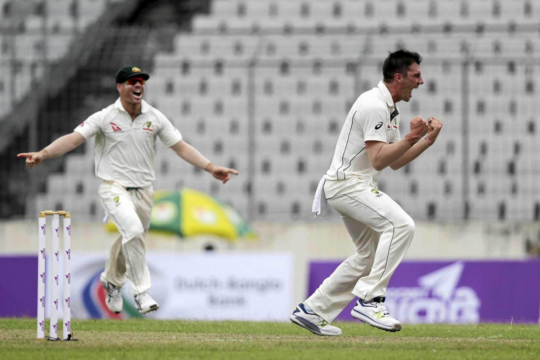 Australia's Pat Cummins, right, and David Warner, left, celebrate the dismissal of Bangladesh's cricketer Sabbir Rahman