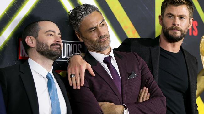 A Taika Waititi sandwich between executive producer Brad Winderbaum and Chris Hemsworth. (Photo by Caroline McCredie/Getty Images)