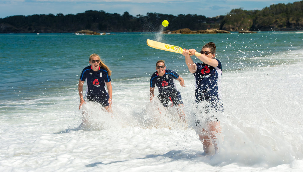 England's opening batter Tammy Beaumont hits out during a game of beach cricket in Coffs Harbour while teammates Sophie Ecclestone and Laura Marsh wait for a catch to come their way.