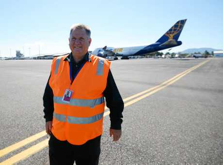Cr Neil Fisher at Rockhampton airport with a 747 on the tarmac.