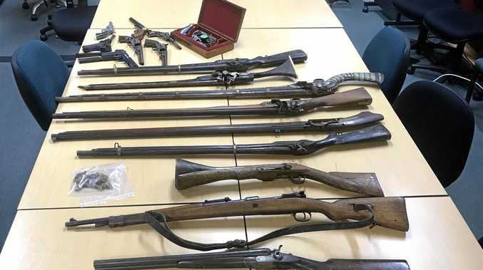 Police seized a number of weapons and a large quantity of drugs in a Friday morning raid.