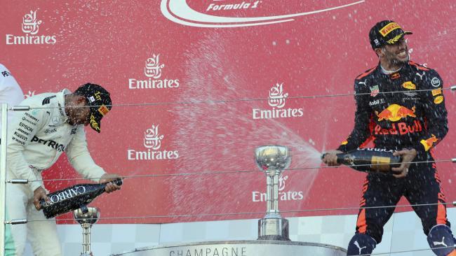 Mercedes driver Lewis Hamilton sprays champagne at Red Bull driver Daniel Ricciardo. (AP Photo/Eugene Hoshiko)