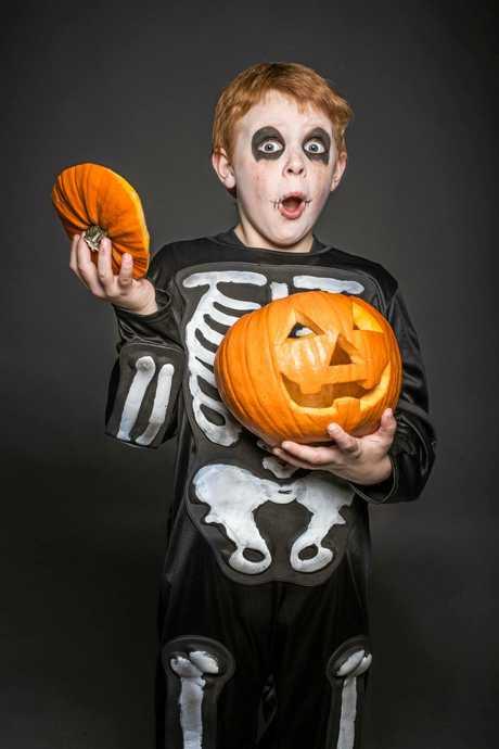 Surprised red hair child in Halloween costume holding a orange pumpkin. Skeleton. Studio portrait over black background