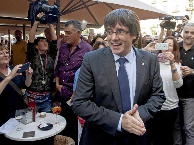 Dismissed Catalan president Carles Puigdemont greets supporters as he leaves a restaurant in Girona on Saturday.