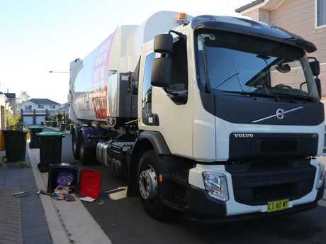 Tight squeeze: Truck driver Michael Roebuck, who didn't knock over this bin, tries to do the right thing by residents. Picture: John Grainger