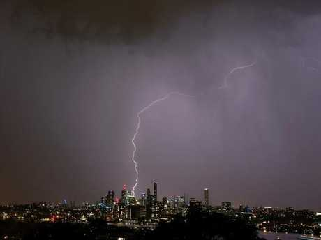 Brisbane City, seen from Hamilton on the city's northside, lights up during a storm on Sunday night. Picture: AAP Image/Steve Pohlner