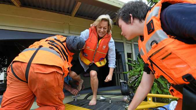 FLOOD RESCUE: One of many residents held by the SES, Michelle Anderson is rescued by the Lismore Unit from her flooded in North Lismore.