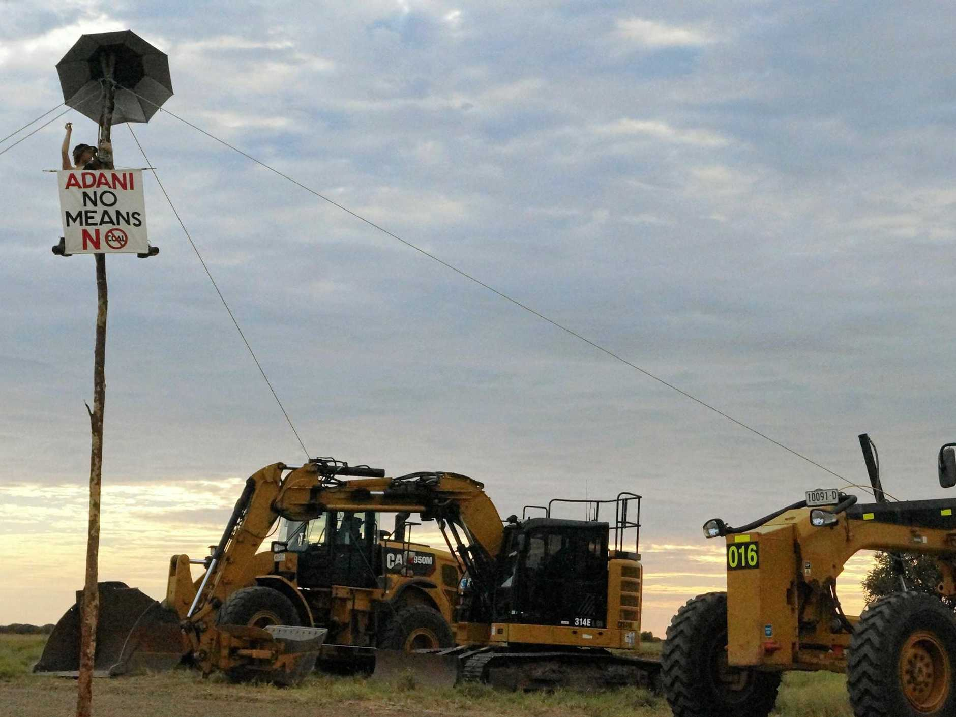 Activist Darcy Poulton is attached to a monopole which is tied to four earthmoving machines at the Adani railway line construction site at Belyando Crossing near Clermont.