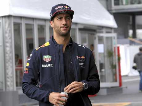 Daniel Ricciardo walks through pit lane after a warm-up session.