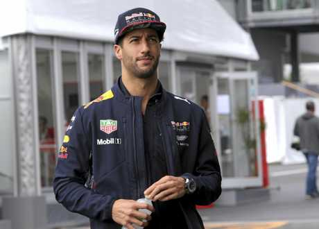 Daniel Ricciardo walks through pit lane after a warm-up session.