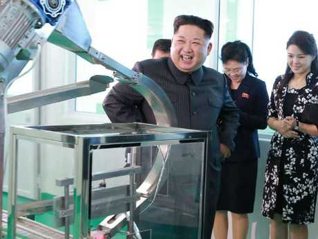 North Korean leader Kim Jong Un visits a cosmetics factory in Pyongyang, North Korea. At second from right is Kim's wife Ri Sol Ju.