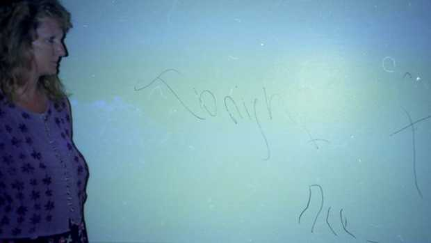 Jill Summerville with graffiti left by the poltergeist. Picture courtesy: Australian Poltergeist