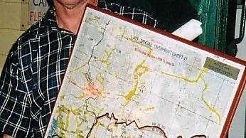 Rockhampton psychologist Bruce Acutt holding a map of the Cawarral area including the section of land he donated for a retreat.