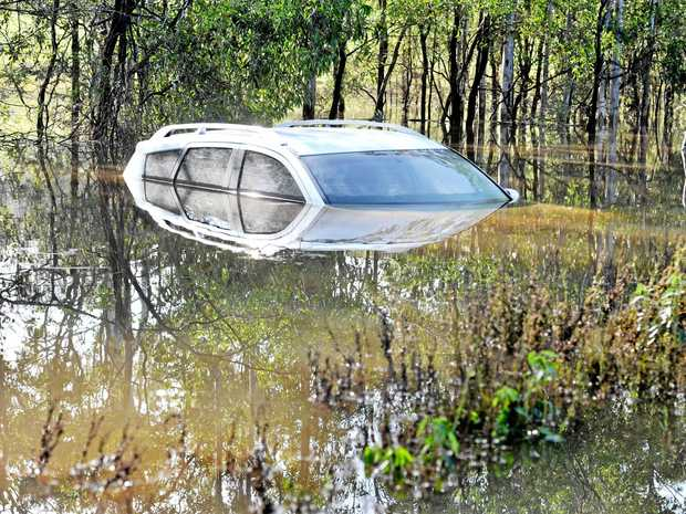 A car that was swept away by flooded waters on Fingerboard Rd near Miriam Vale in 2014. The road was closed because of flooding just weeks ago