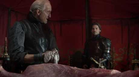 Tywin guts a stag while Jaime watches and listens.