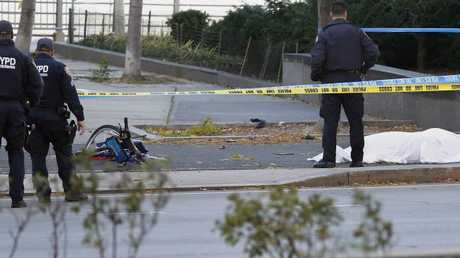 A New York Police Department officer stands next to a body covered under a white sheet near a mangled bike along a bike path Tuesday Oct. 31, 2017, in New York. Picture: AP Photo/Bebeto Matthews