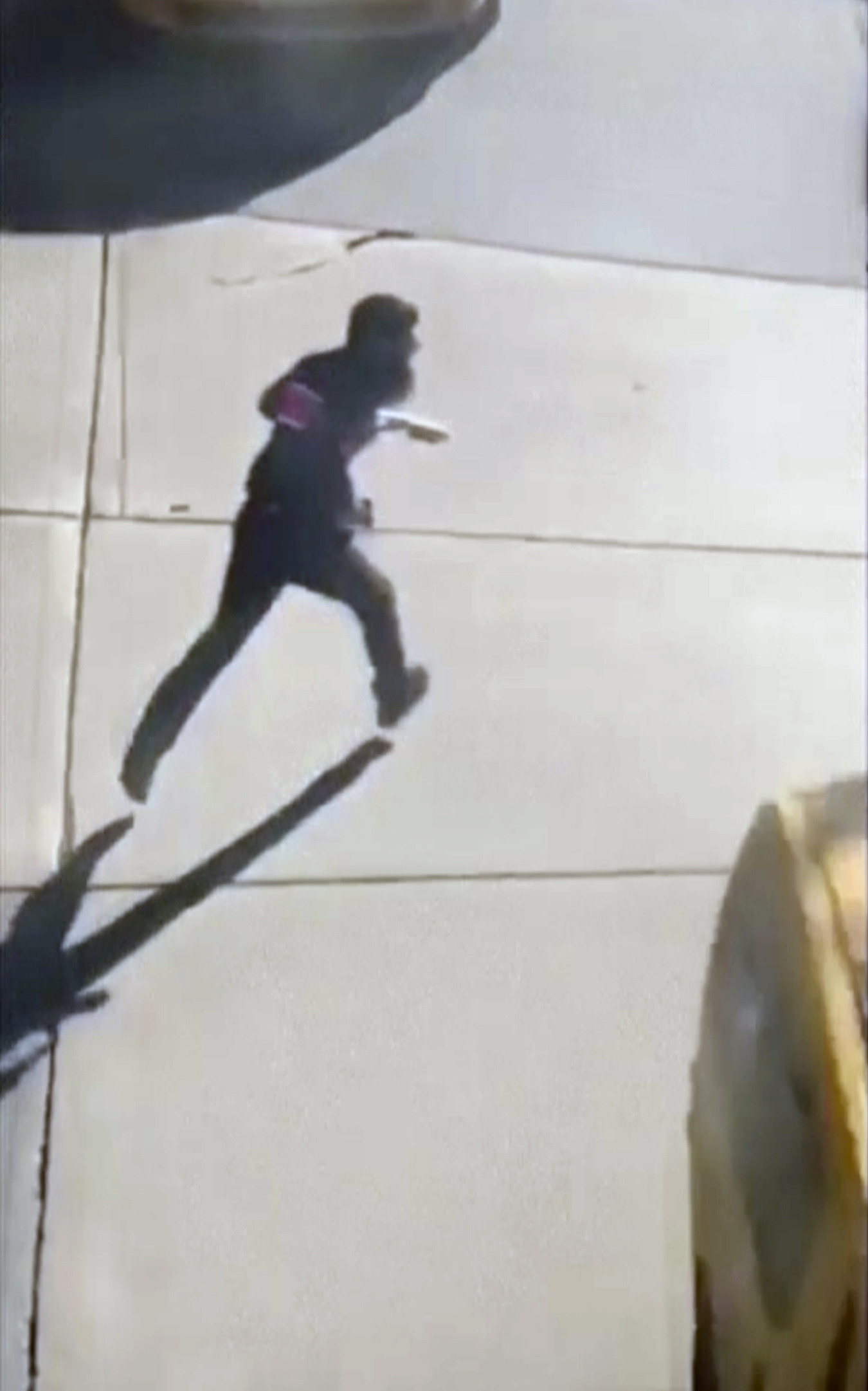 This image made from a video provided by Tawhid Kabir shows the suspect in a deadly attack running across the street with a fake gun in each hand on Tuesday, Oct. 31, 2017, in New York. The man mowed down pedestrians and cyclists along a busy bike path near the World Trade Center memorial on Tuesday, before he was shot in the abdomen by police after jumping out of the truck, authorities said. (You