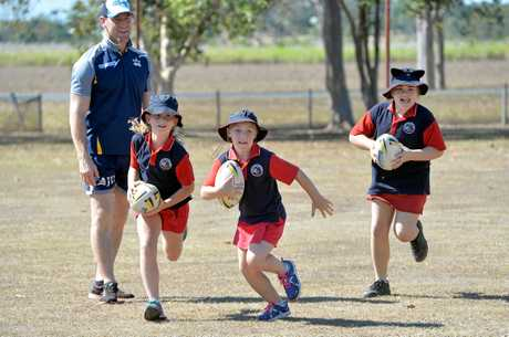 Children playing a game of footy with the Cowboys.