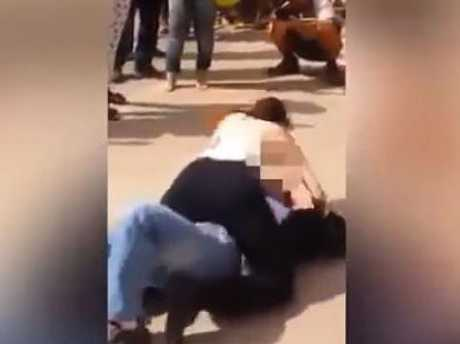 Shocked onlookers watched as the enraged woman took off her top and began hitting the man with her breasts. Picture: FocusOnNews