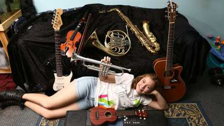 Elliena Escott, 14 from Surfers Paradise, plays 11 instruments including the trumpet, the French horn, guitar, drums, piano and saxophone. Picture: Glenn Hampson