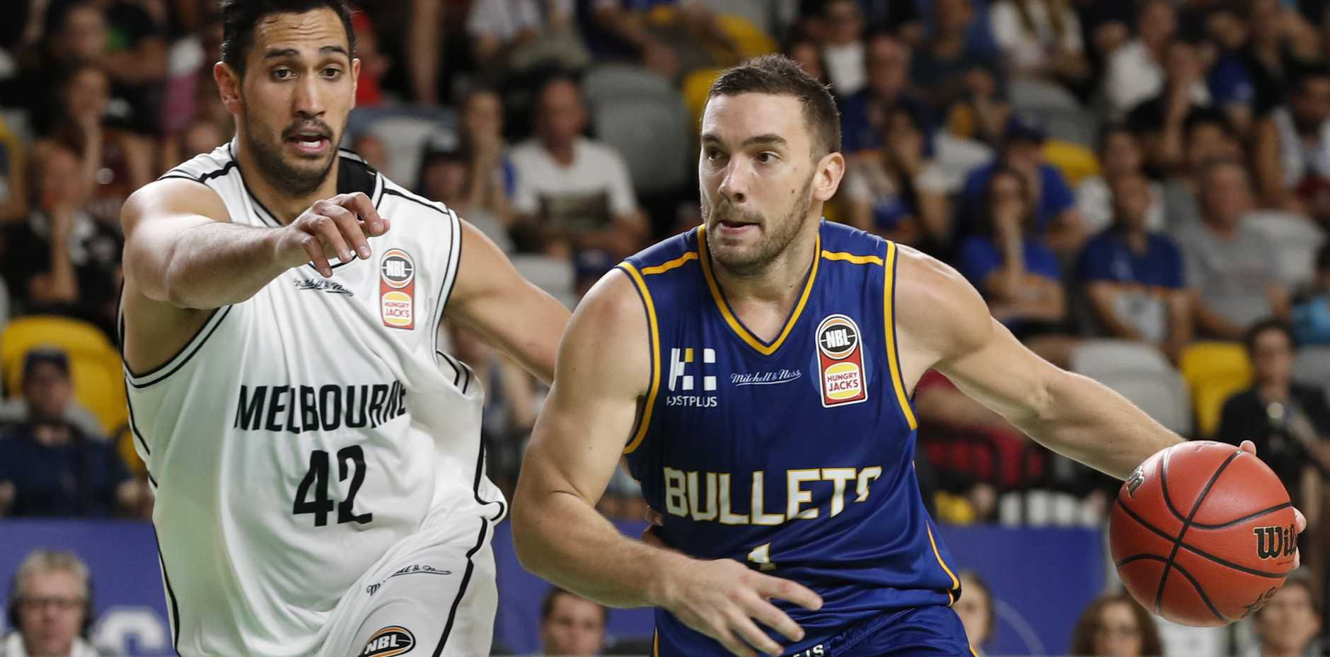 Adam Gibson (right) of Brisbane Bullets tries to dribble past Tai Wesley of Melbourne United.