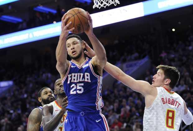 The Philadelphia 76ers' Ben Simmons pulls in a rebound over the Atlanta Hawks' Luke Babbitt.